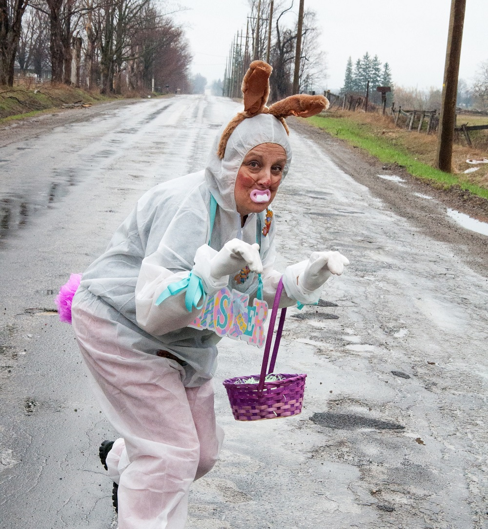 woman dressed up as an easter bunny creeping down a road
