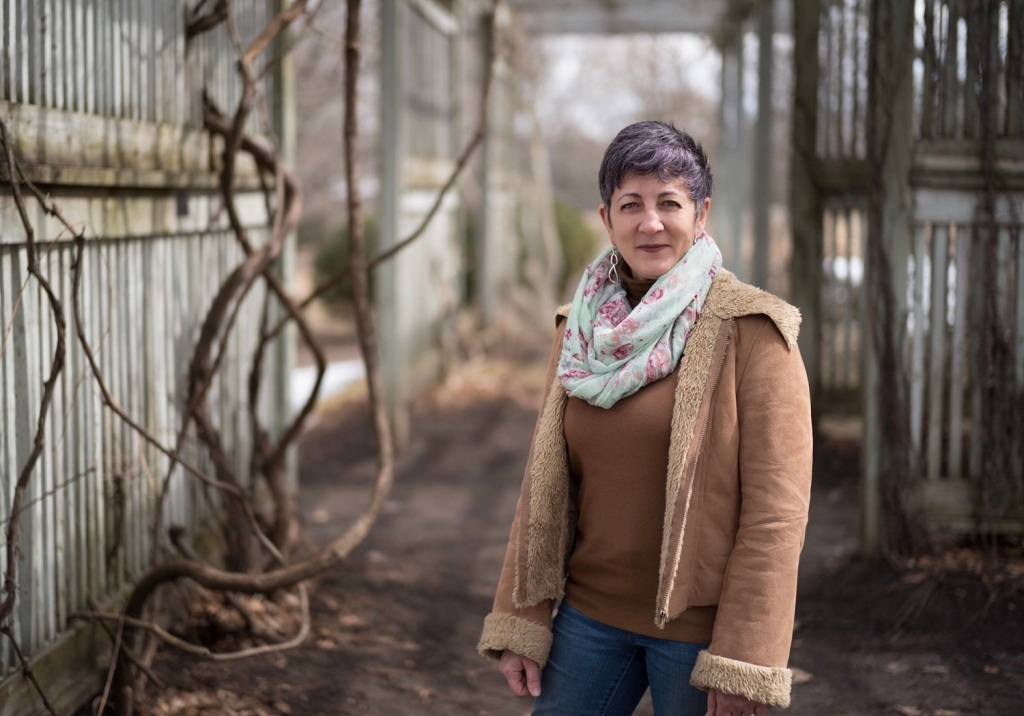 woman with short purple hair stands in park, wearing neutral colours, half smile