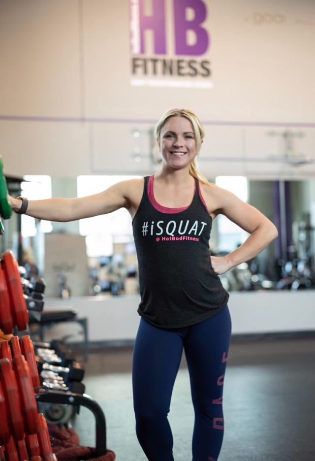 young woman with blonde hair in ponytail stands in workout studio, hand on one hip