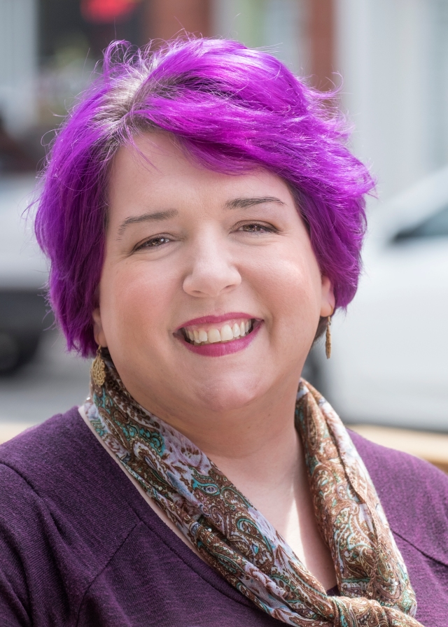woman with purple hair smiles at the camera