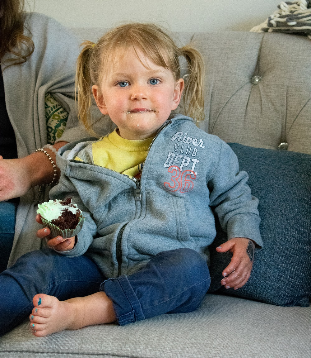 young girl eating a cupcake on a couch