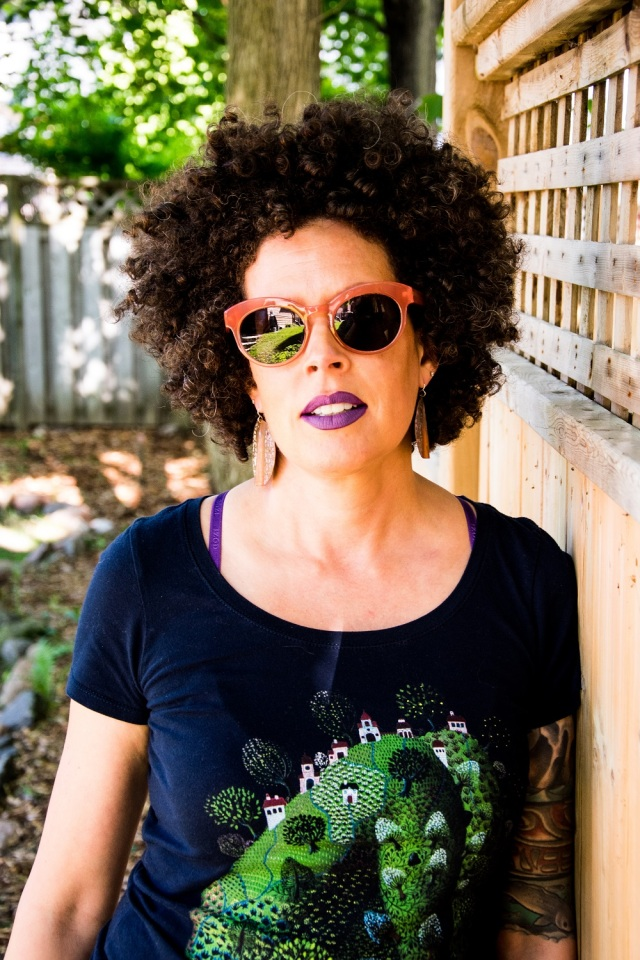 woman with big curly hair, large orange sunglasses, purple lipstick and t-shirt stands outside