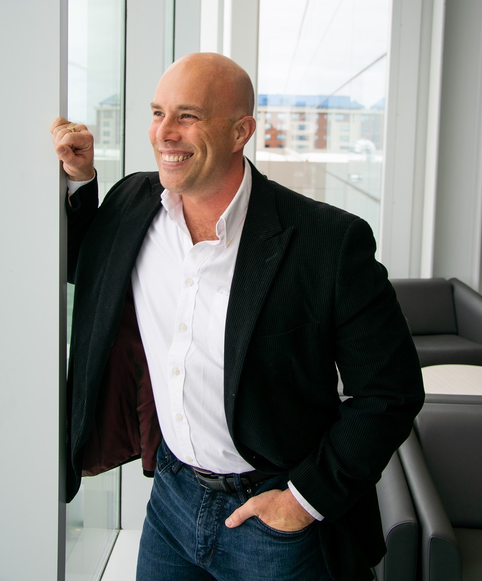 man standing in bank of windows wearing jeans, white shirt and black suit jacket, smiling