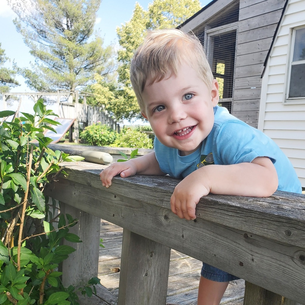 toddler smiling, leaning over a wooden small deck