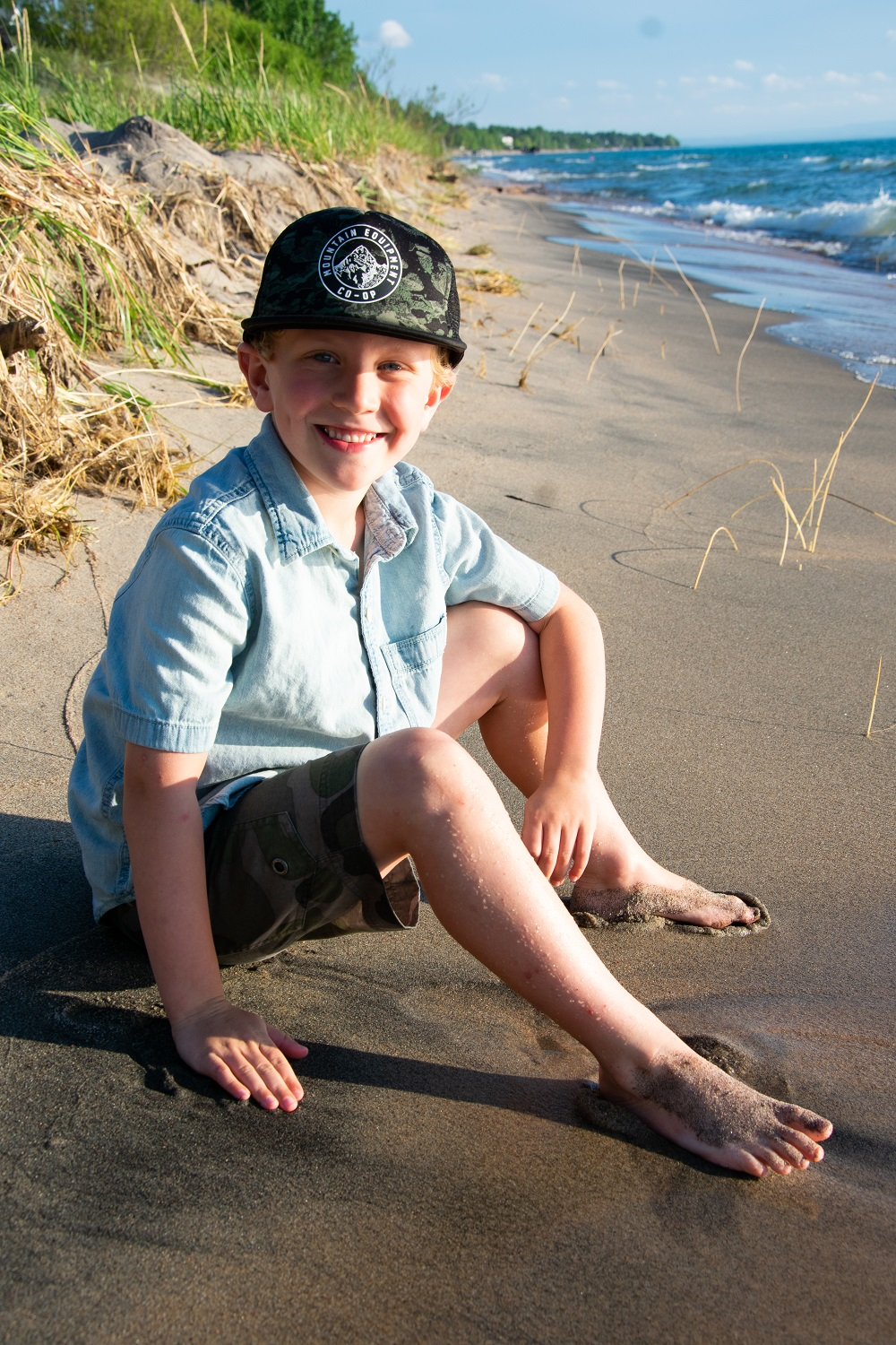 young boy sitting on beach smiling at camera wearing hat, shirt and shorts