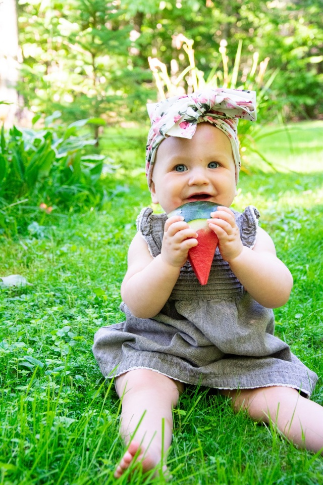young toddler sitting in the grass eating watermelon