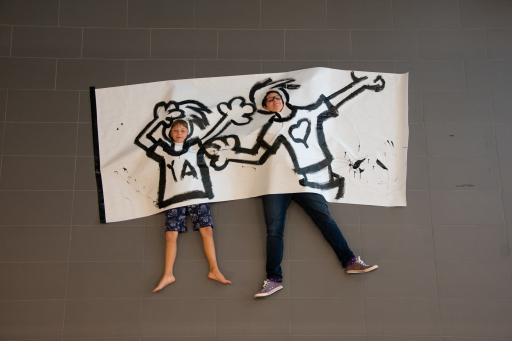young kid and mom laying under cartoon drawing on grey floor